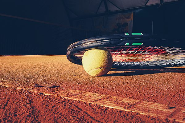 Tennis racket and ball on dirt court