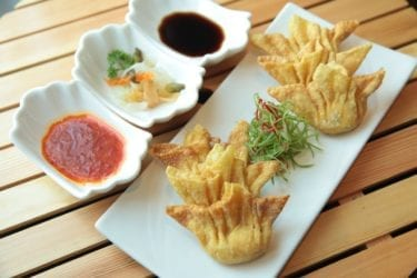 Wontons with dipping sauce on wooden table
