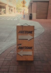 Sign on sidewalk, awesome to the right and less awesome to the left