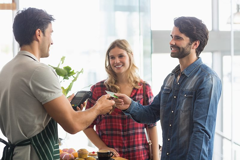 Male and female customers paying a merchants with a credit card