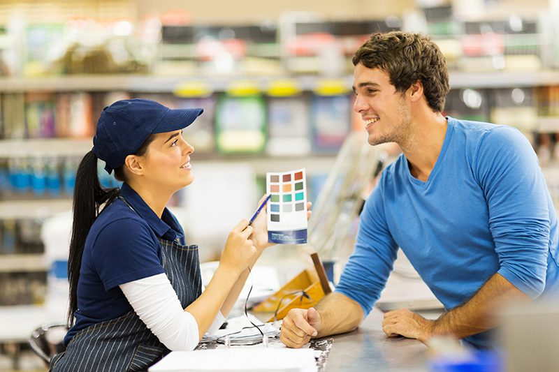 Male customer talking to paint specialist woman in a store