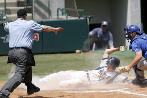 Baseball Ump calling safe as player slides into home